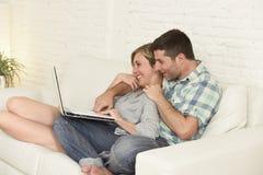 Beaux couples dans l'amour sur le divan ainsi que l'ordinateur portable heureux à la maison utilisant l'Internet Images libres de droits