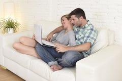 Beaux couples dans l'amour sur le divan ainsi que l'ordinateur portable heureux à la maison utilisant l'Internet Photos stock