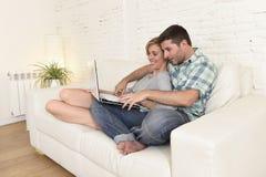 Beaux couples dans l'amour sur le divan ainsi que l'ordinateur portable heureux à la maison utilisant l'Internet Photo libre de droits