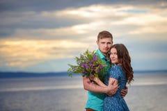 Beaux couples dans l'amour sur le fond de ciel de coucher du soleil Images stock
