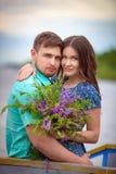 Beaux couples dans l'amour sur le fond de ciel de coucher du soleil Images libres de droits
