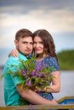 Beaux couples dans l'amour sur le fond de ciel de coucher du soleil Photo libre de droits
