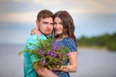 Beaux couples dans l'amour sur le fond de ciel de coucher du soleil Photo stock