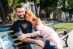 Beaux couples de datation étreignant sur un banc photographie stock libre de droits