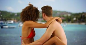 Beaux couples de métis se tenant s'asseyant par l'eau tropicale Image stock