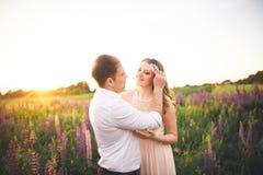 Beaux couples de mariage, amour sur le coucher du soleil Fielf avec des fleurs Photo libre de droits