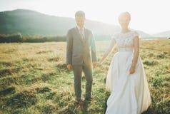 Beaux couples de mariage, amour sur le coucher du soleil Fielf avec la vue sur des montagnes Images libres de droits