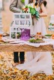 Beaux couples de mariage embrassant dans premier plan de table de vintage de forêt d'automne le rétro Photographie stock libre de droits