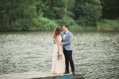 Beaux couples de mariage, jeune mariée, marié embrassant et posant sur le pont près du lac Photo libre de droits
