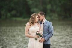 Beaux couples de mariage, jeune mariée, marié embrassant et posant sur le pont près du lac Photographie stock