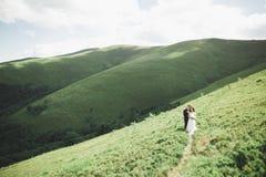 Beaux couples de mariage, jeunes mariés, dans l'amour sur le fond des montagnes Image libre de droits