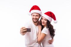 Beaux couples de portrait dans des chapeaux de Santa dans l'amour prenant l'autoportrait romantique Image libre de droits