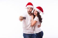 Beaux couples de portrait dans des chapeaux de Santa dans l'amour prenant l'autoportrait romantique Photographie stock libre de droits