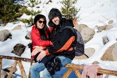 Beaux couples de sourire étreignant et souriant dans la montagne d'hiver Images stock