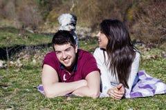 Beaux couples de sourire ayant l'amusement avec leur chien blanc extérieur Images libres de droits