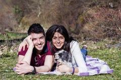 Beaux couples de sourire ayant l'amusement avec leur chien blanc extérieur Photos libres de droits