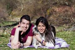 Beaux couples de sourire ayant l'amusement avec leur chien blanc extérieur Image stock
