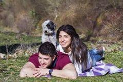 Beaux couples de sourire ayant l'amusement avec leur chien blanc extérieur Images stock