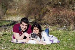 Beaux couples de sourire ayant l'amusement avec leur chien blanc extérieur Photo stock