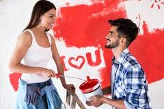 Beaux couples de sourire peignant la nouvelle maison, rénovation de nouvelle maison Photographie stock