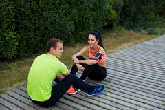 Beaux couples de sport se reposant après la séance d'entraînement se reposant en beau parc Photographie stock libre de droits