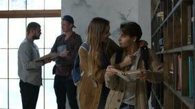 Beaux couples des étudiants apprenant dans la bibliothèque banque de vidéos