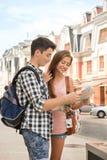 Beaux couples des touristes tenant une carte dedans Image libre de droits