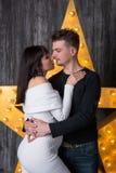 Beaux couples devant une étoile rougeoyante Grossesse Image stock