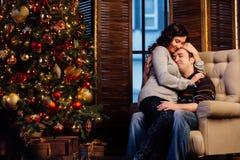 Beaux couples embrassant dans le fauteuil près de l'arbre de Noël à la soirée du Nouveau an Image stock