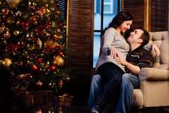 Beaux couples embrassant dans le fauteuil près de l'arbre de Noël à la soirée du Nouveau an Images stock