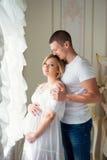 Beaux couples enceintes doux près des rideaux de Tulle Photographie stock