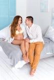 Beaux couples enceintes heureux ensemble attendant un enfant Homme et femme dans l'intérieur grec blanc de chambre à coucher de s Photos libres de droits