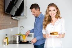 Beaux couples faisant des crêpes pour le petit déjeuner Photos stock