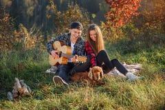 Beaux couples heureux dans des vêtements sport avec la guitare et leur chien ayant le repos sur le pique-nique dans le parc photo libre de droits