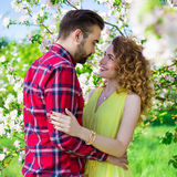 Beaux couples heureux dans l'amour posant dans le jardin de floraison Photos stock