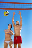 Beaux couples heureux jouant le volleyball Photos stock