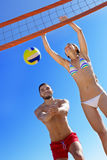 Beaux couples heureux jouant le volleyball Photo stock
