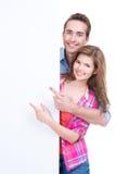 Beaux couples heureux montrant à la bannière. Photographie stock libre de droits