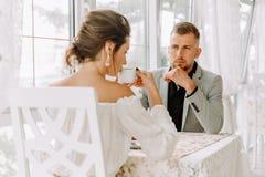 Beaux couples heureux se reposant dans un restaurant et parler Image stock