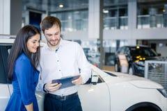 Beaux couples heureux se tenant près de leur nouvelle voiture Photos libres de droits