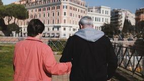 Beaux couples heureux supérieurs romantiques de vue arrière marchant ensemble tenant des mains des vacances en automne tôt Rome,  banque de vidéos