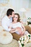 Beaux couples, jeune femme enceinte et homme étreignant avec des baisers d'amour, se reposant sur le lit, dans un intérieur de ma Photos libres de droits