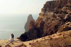 Beaux couples jeune mariée magnifique dans la robe de mariage posant avec le marié élégant sur le coût de mer photos stock