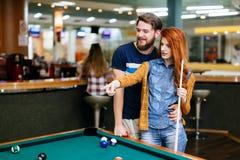 Beaux couples jouant des billards Photos stock
