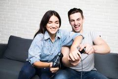 Beaux couples jouant des jeux vidéo sur la console ayant l'amusement à la maison images libres de droits