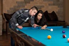 Beaux couples jouant la piscine Images stock