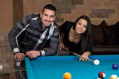 Beaux couples jouant la piscine Photographie stock
