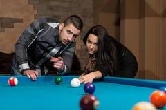 Beaux couples jouant la piscine Photo stock