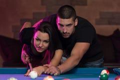 Beaux couples jouant la piscine Image libre de droits