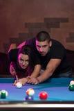 Beaux couples jouant la piscine Photos stock